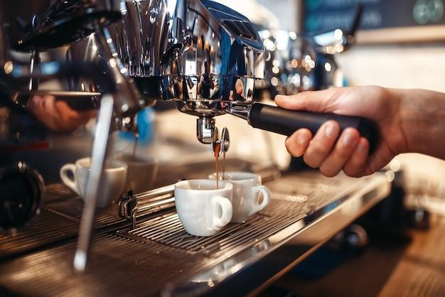 Ręka baristy nalewa napój z ekspresu do kawy