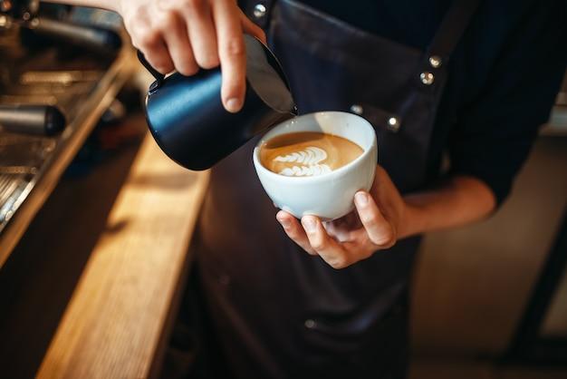 Ręka baristy nalewa śmietankę do filiżanki kawy