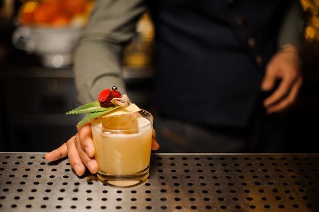 Ręka barmana dekorująca świeży koktajl alkoholowy
