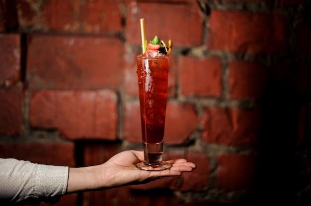 Ręka barmana trzyma szklankę świeżego letniego koktajlu szewcowego ozdobionego truskawką i miętą