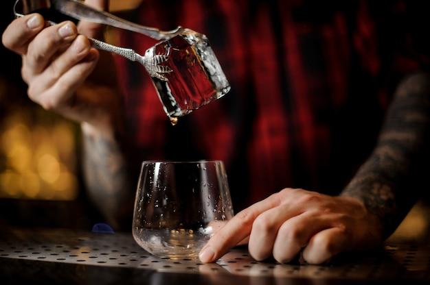 Ręka barmana umieszczenie dużej kostki lodu w dof whisky za pomocą szczypiec