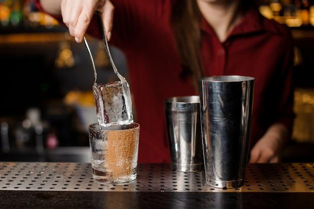 Ręka barmana wprowadzenie dużej kostki lodu do kieliszka koktajlowego
