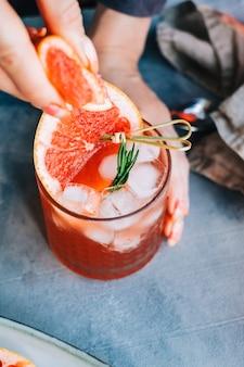 Ręka barmana wyciska sok ze świeżego grejpfruta w lemoniadzie koktajlowej z lodem i rozmarynem.