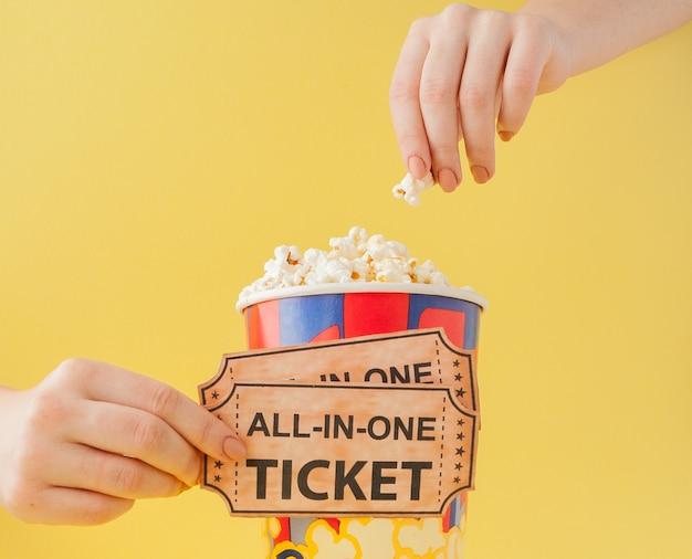 Ręka bierze bilety do kina i popcorn z papierowego kubka na żółtym tle. kobieta je popcorn. koncepcja kina. leżał płasko.