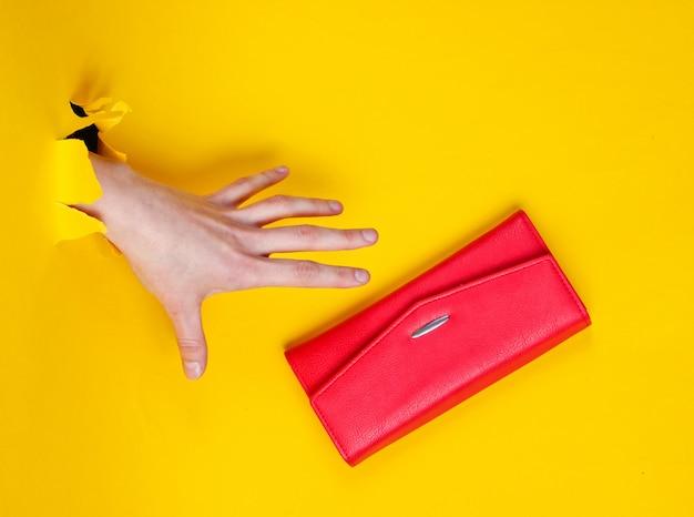 Ręka bierze czerwoną torebkę przez rozdarty żółty papier. minimalistyczna koncepcja kreatywnej mody