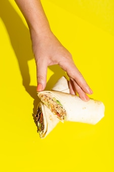 Ręka bierze doner roll shawarma z kurczakiem i warzywami na żółtym wysokiej jakości zdjęciu