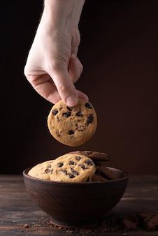 Ręka bierze jeden czekoladowy plik cookie z talerza na ciemnym drewnianym stole
