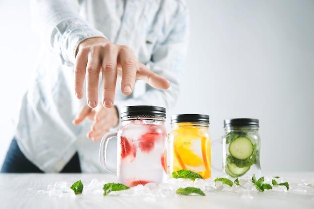 Ręka bierze jeden z rustykalnych słoików z zimnymi świeżymi, domowymi lemoniadami z truskawek, pomarańczy, ogórka, lodu i mięty