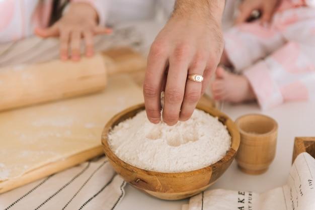 Ręka bierze mąkę z drewnianej miski