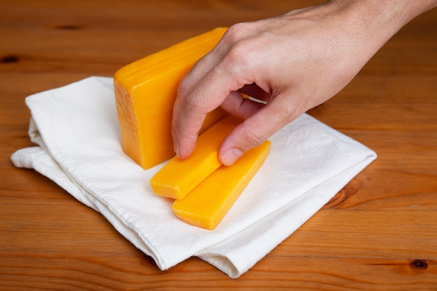 Ręka bierze żółtego ser kłaść na białym płótnie
