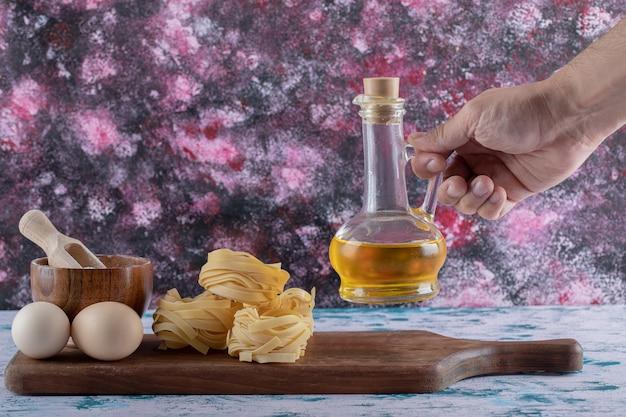 Ręka, biorąc butelkę oleju z drewnianej deski.