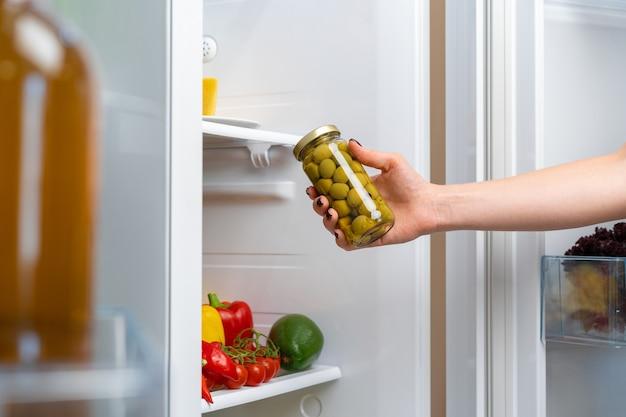 Ręka biorąc słoik oliwek z lodówki z bliska