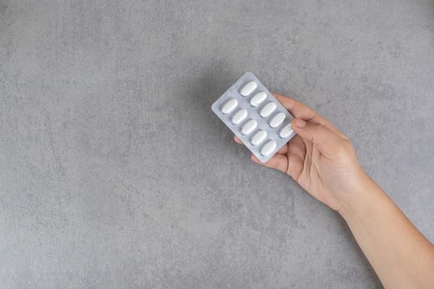 Ręka biorąca białą pigułkę na szarej powierzchni