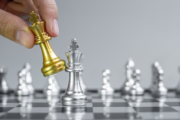 Ręka biznesmen przenoszenie złota figura szachowego króla podczas konkursu szachownicy.