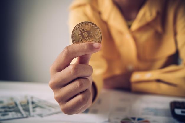 Ręka biznesmen trzyma złocistego bitcoin