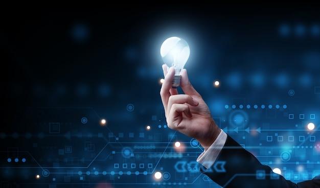 Ręka biznesmen trzymając klasyczną żarówkę, rozwiązanie sukcesu biznesowego i koncepcja kreatywności.