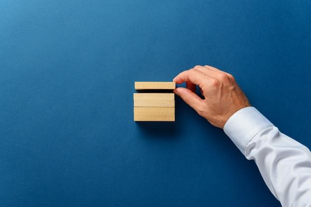 Ręka biznesmen układa drewniane kołki