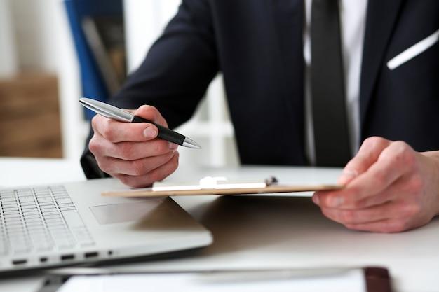 Ręka biznesmen w kostiumu podpisywania dokumencie