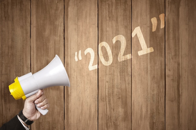 Ręka biznesmen z megafonem ogłasza szczęśliwego nowego roku. szczęśliwego nowego roku 2021