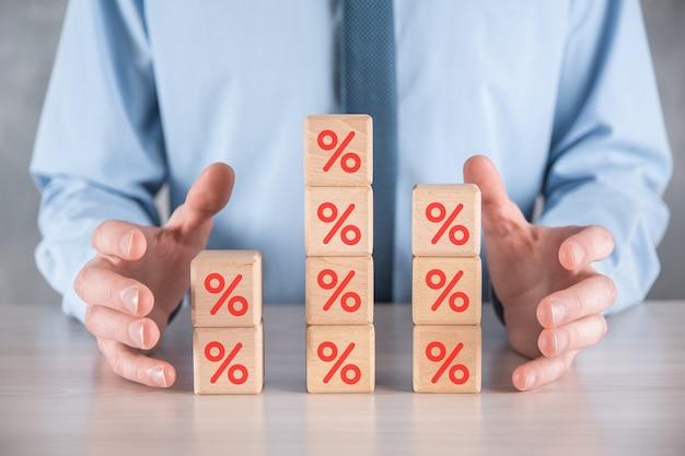Ręka biznesmena bierze drewniany sześcian przedstawiający ikonę symbolu procentu. koncepcja stóp procentowych finansowych i kredytów hipotecznych.