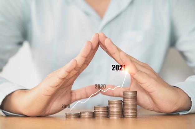 Ręka biznesmena chroniąca układanie monet z wirtualnym wykresem, zysk z inwestycji biznesowych i wzrost oszczędności w koncepcji 2021.