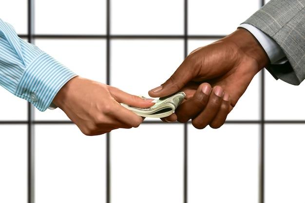 Ręka biznesmena daje kobiecie dolary. ręce przechodząc amerykańską walutę. właściwa inwestycja do zrobienia. pieniądze to najlepsza motywacja.