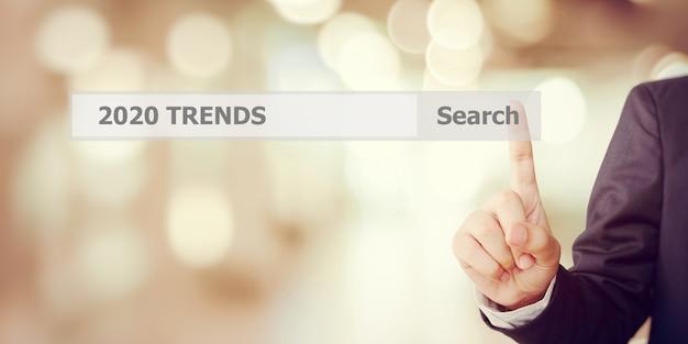 Ręka biznesmena dotykając paska wyszukiwania trendów 2020 ponad rozmycie biura
