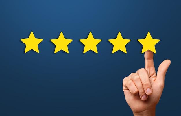 Ręka biznesmena dotykająca pięciogwiazdkowego symbolu, aby zwiększyć ocenę koncepcji firmy,