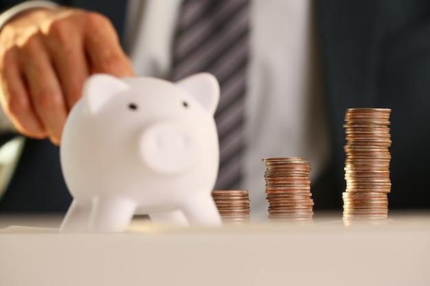Ręka biznesmena kładzenia szpilki pieniądze w świnię