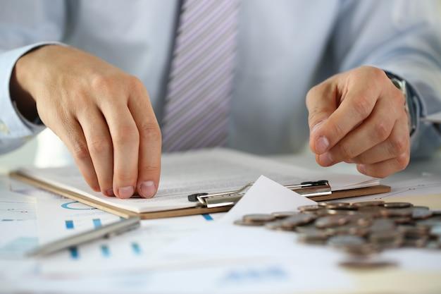 Ręka biznesmena kładzenia szpilki pieniądze zbliżenie