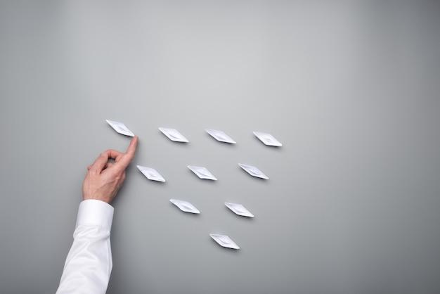 Ręka biznesmena pchająca jedną z papierowych origami łódek do przodu, aby wyróżnić się z grupy.