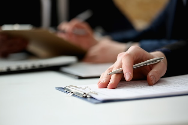 Ręka biznesmena podpisywania dokument z piórem