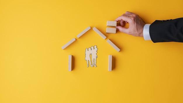 Ręka biznesmena robiąca dom z drewnianych klocków wokół wyciętej z papieru sylwetki rodziny..