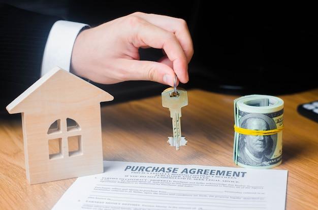 Ręka biznesmena trzyma klucze do umowy na zakup nieruchomości