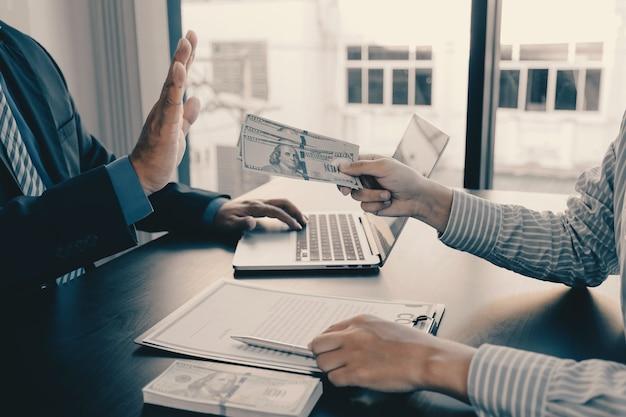 Ręka biznesmena trzymająca banknot dolarowy za łapówkę urzędnicy państwowi podnoszą rękę odmawiając pieniędzy