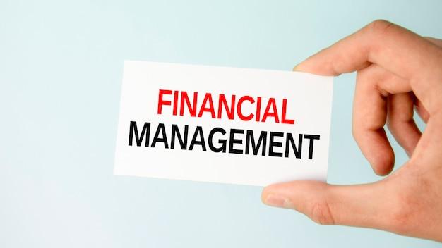 Ręka biznesmena trzymająca papierową wizytówkę z tekstem zarządzanie finansami, zbliżenie jasnoniebieskie tło, koncepcja biznesowa