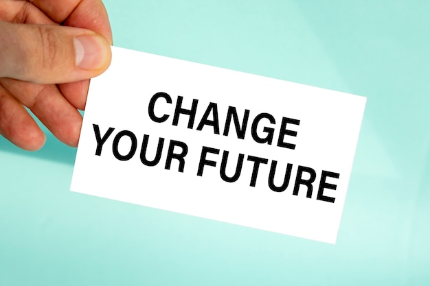 Ręka biznesmena trzymająca papierową wizytówkę z tekstem zmienia swoją przyszłość, zbliżenie jasnoniebieskie tło, koncepcja biznesowa