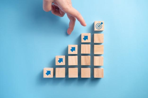 Ręka biznesmena układanie drewnianych klocków schody z ikoną strzałki, koncepcja planowania biznesowego.