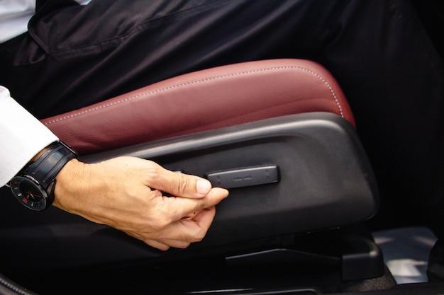 Ręka biznesmena umieścić przycisk regulacji poziomu fotelika samochodowego.