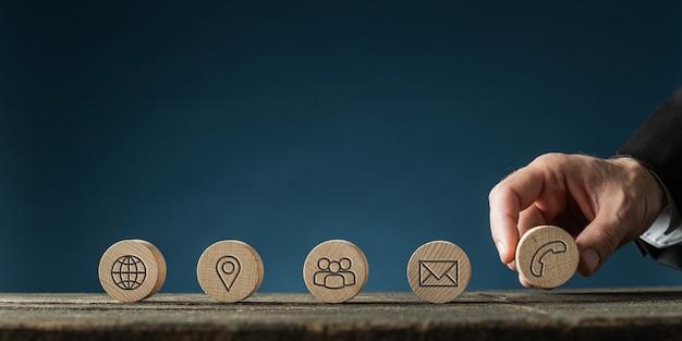 Ręka biznesmena umieszczająca pięć drewnianych kółek z ikonami kontaktu i informacji w rzędzie na rustykalnym drewnianym biurku.