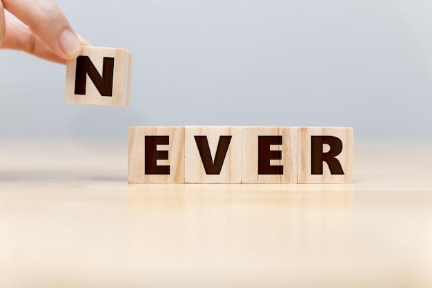 """Ręka biznesmena usuwa drewniany klocek """"n"""" ze sformułowania """"nigdy"""" nie stanie się """"nigdy"""", rozwiązania do sukcesu biznesowego i koncepcji pracy zespołowej."""