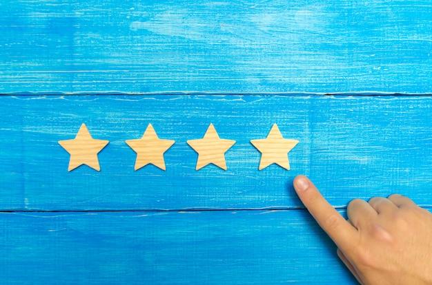 Ręka biznesmena w garniturze wskazuje na czwartą gwiazdę. zdobądź piątą gwiazdkę
