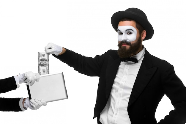 Ręka biznesmena w postaci mima wyciąga pieniądze z komputera typu tablet