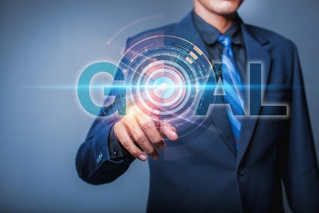 Ręka biznesmena wskazująca cyfrowy projekt słowa celu