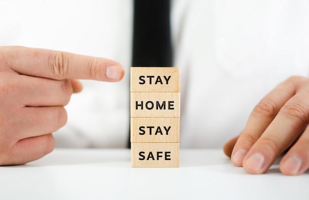Ręka biznesmena wskazującego na stos drewnianych klocków ze znakiem bądź w domu bądź bezpieczny, zachęcając ludzi do pozostania w domu