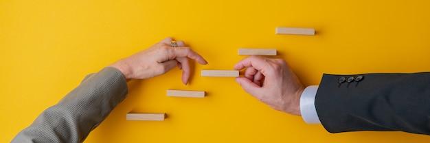 Ręka biznesmena wspierającego krok w koncepcyjne schody dla jego partnerki chodzić palcami w górę. obraz szerokokątny.