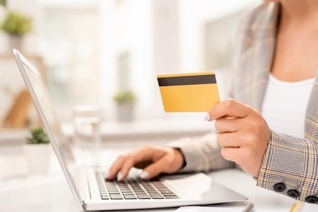 Ręka biznesmena z plastikową kartą wprowadzania jej danych osobowych podczas składania zamówienia w sklepie internetowym przez miejsce pracy