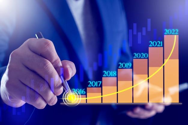 Ręka biznesmena z wykresem 100 koncepcji sukcesu bankowości i finansów na wykresie świecowym