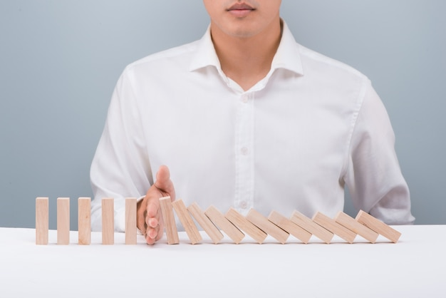 Ręka biznesmena zatrzymała domino w ciągłym upadku