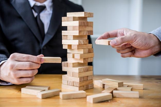 Ręka biznesmeni wprowadzania i ciągnięcie bloku drewna na wieży